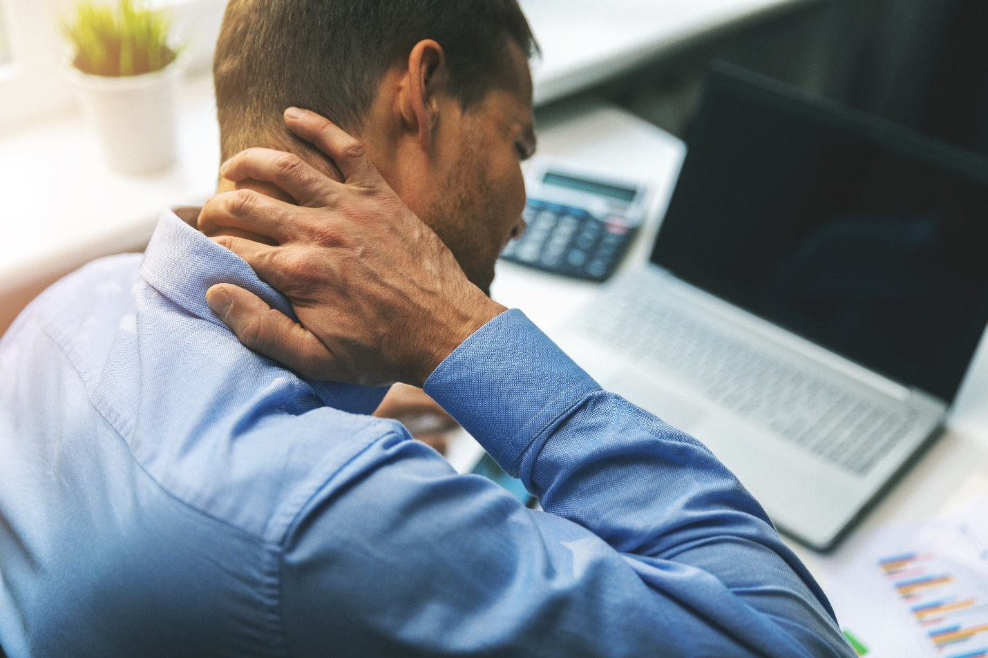 man suffering from neck and back pain while working with computer