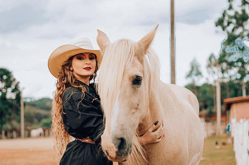 Stylish women standing near horse